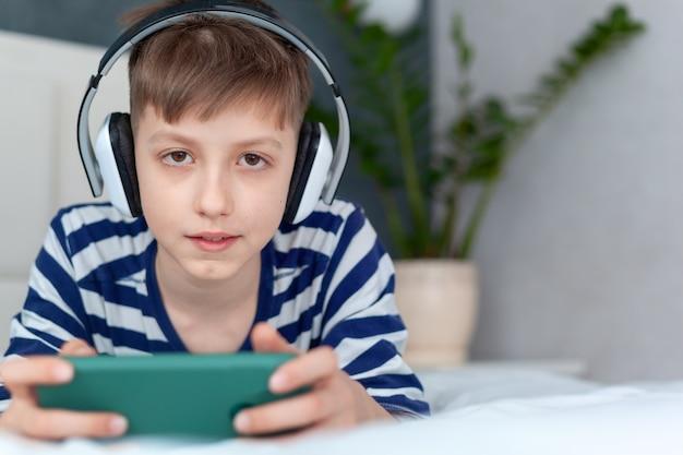 Милый ребенок мальчик в наушниках, играя на смартфоне на кровати в гостиной. образование, свободное время, технологии и концепция интернета