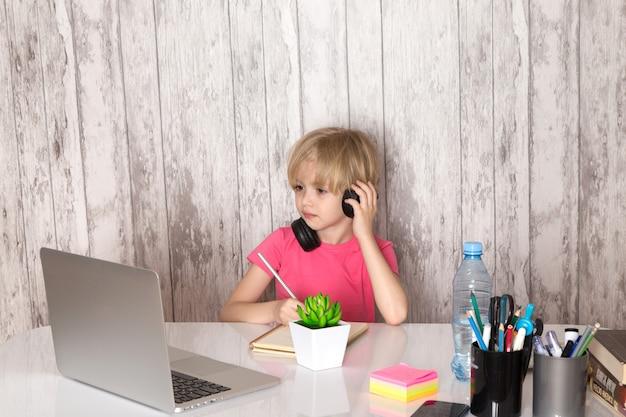 灰色の壁に緑の植物ボトルペンと一緒にテーブルに灰色のラップトップを使用してピンクのtシャツ黒イヤホンでかわいい子少年