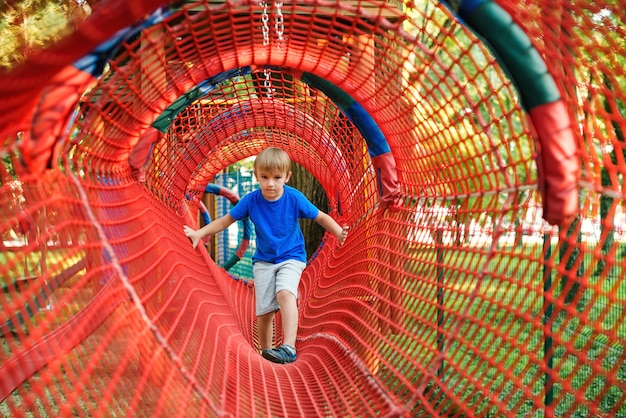 Cute child boy overcomes obstacles in rope tunnel outdoors. modern amusement park for kids. healthy and happy childhood.