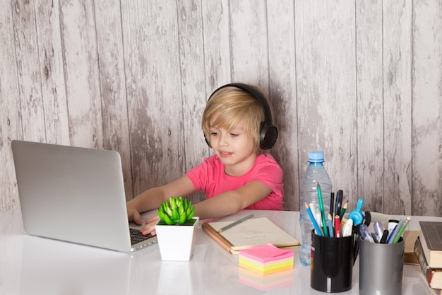 Ragazzo carino bambino in maglietta rosa auricolari neri con laptop grigio sul tavolo insieme a penne bottiglia pianta verde sul muro grigio