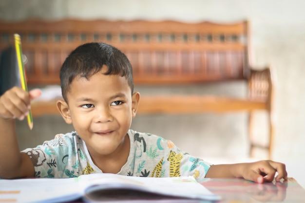 家で勉強して考えているかわいい男の子。