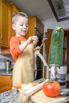 부엌에 있는 냄비에 큰 호박과 다른 야채를 요리하는 앞치마를 가진 귀여운 어린이 요리사