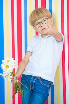 Cute child close up portrait on colorful  . adorable little boy standing near to the wall. kid holding a bouquet of flowers.