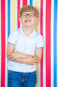 Портрет милого ребенка близкий поднимающий вверх на красочном. прелестный маленький мальчик стоял рядом со стеной.
