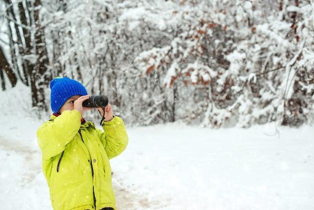 雪に覆われた森のかわいい子供探検家。家族での休暇、雪の日、そして幸せな子供時代。単眼を探している子供。家族の冬休み。自然の中で冬の楽しみ。冬の森を歩いて幸せな子。