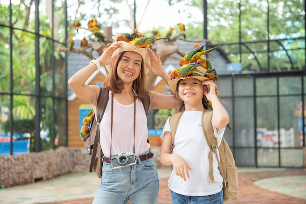 Cute child feeling happy and smiles with her mother while playing with parrot bird.