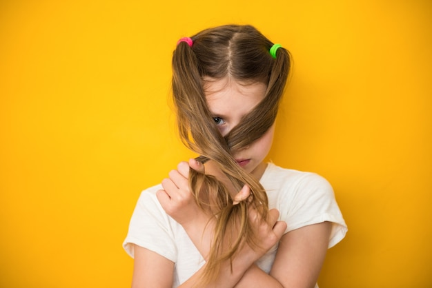 Cute child girl closes her face with her hair. menstrual period for the first time concept