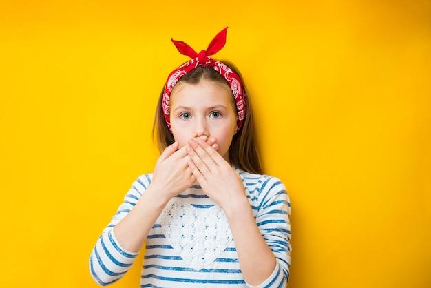 귀여운 아이 소녀는 아무것도 부끄러워 그녀의 손으로 그녀의 입을 닫습니다