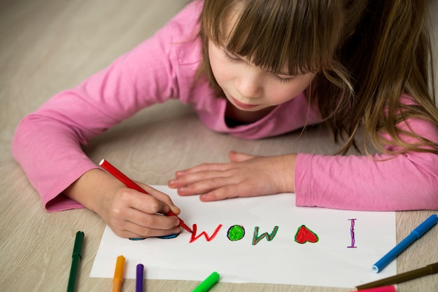 Cute child girl drawing with colorful crayons