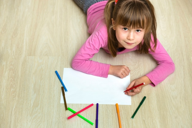 Cute child girl drawing with colorful pencils crayons on white paper. art education, creativity concept.