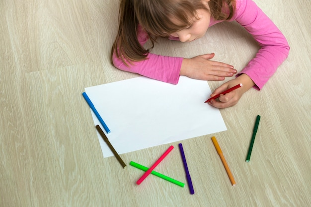 Cute child girl drawing with colorful pencils crayons on a white paper