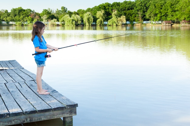 Cute child girl fishing from wooden pier on a lake. family leisure activity during summer sunny day.
