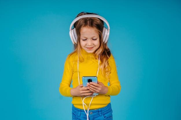 かわいい子の女の子は青い背景で隔離のスマートフォンを保持します