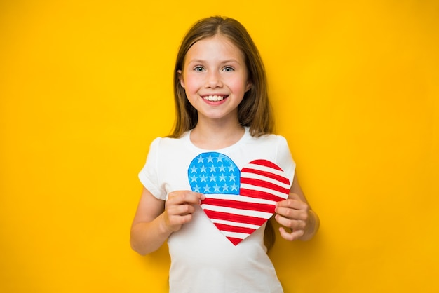 Cute child girl holds an american flag near her heart. patriotism, independence day, flag day concept. memorial day