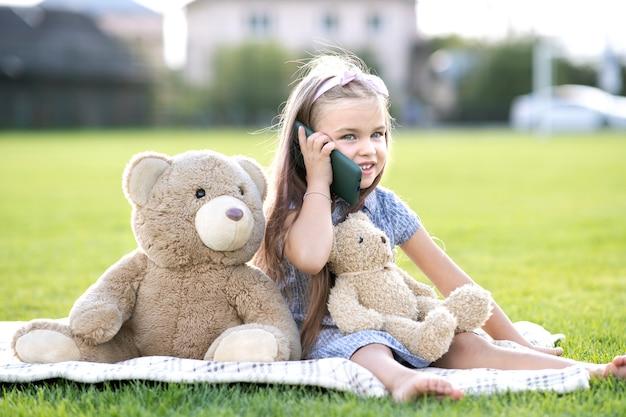 夏の屋外で携帯電話で話している彼女のテディベアのおもちゃと緑の芝生の芝生の上の夏の公園で休んでいるかわいい子供の女の子。