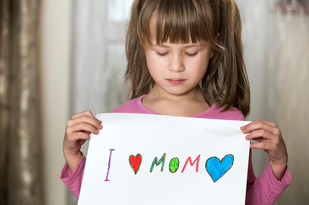 Cute child girl wit sheet of paper with colorful crayons painted words i love mom. art education, creativity concept.