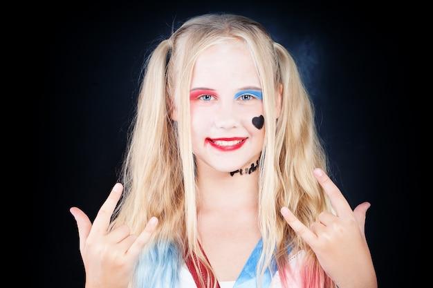 Милая детская девочка с макияжем на хэллоуин, весело проводящая время