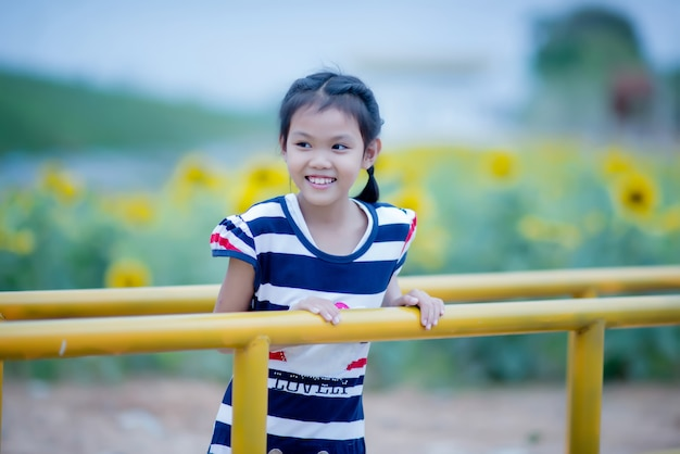 Cute child girl with sunflower in summer field