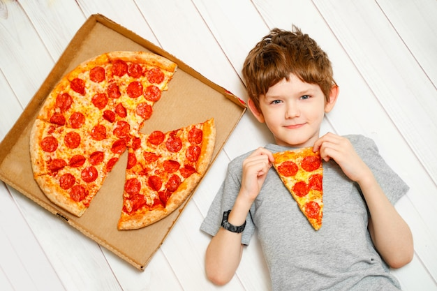 Cute child holding a slices of pizza lying on the wooden floor