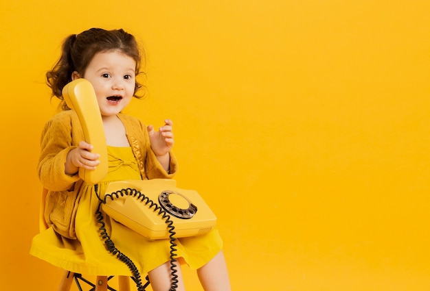 Cute child holding telephone while posing