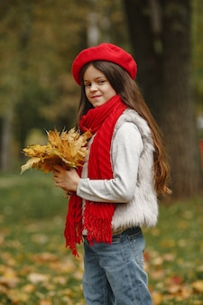 빨간 베레모에 귀여운 아이. 우아한 아가씨. 잎의 꽃다발을 가진 아이입니다.