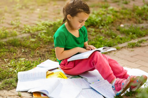 A cute child is reading  in the park.