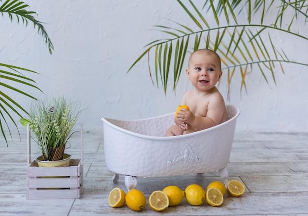 Милый ребенок сидит в белой ванне с лимонами на белом фоне с растениями. веселое плавание