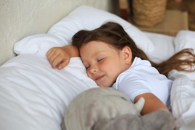かわいい子の小さな女の子がおもちゃの象と一緒にベッドで寝ています。