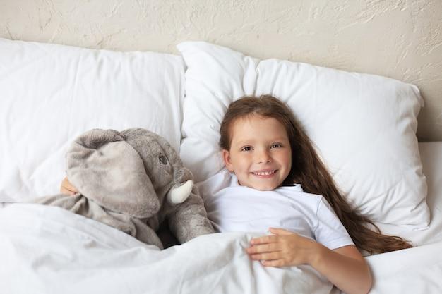 かわいい子の小さな女の子が目を覚まし、おもちゃの象と一緒にベッドに横たわっています。