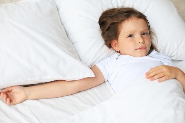 かわいい子の小さな女の子が目を覚まし、ベッドに横たわっています。