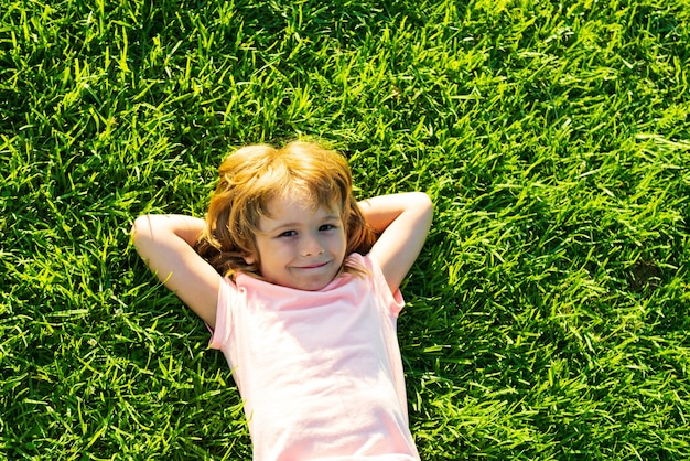 Cute child lying on grass background. happy freedom kid boy enjoying on field and dreaming. unity with nature.