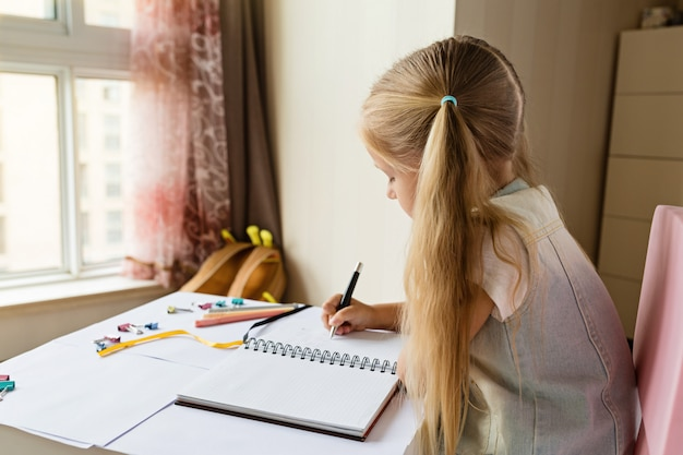 Cute child makes homework at home.