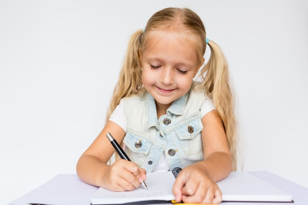 Cute child makes homework on white background.