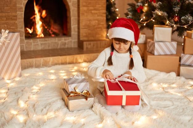 Bambino carino che apre la scatola regalo di babbo natale, indossa un maglione bianco e un cappello di babbo natale, posa in una stanza festiva con camino e albero di natale mentre è seduto su un pavimento morbido.
