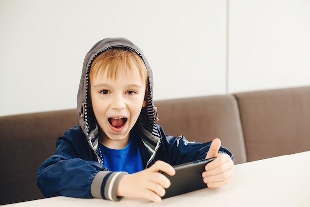 スマートフォンでビデオゲームをしているかわいい子供。感情的な幸せな少年は携帯電話でゲームをします。ポジティブな感情を持つ小さなゲーマー。電話やビデオゲームの子供中毒。携帯電話を持つ子供。