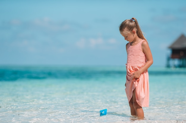 Cute child playing with paper boats in a sea