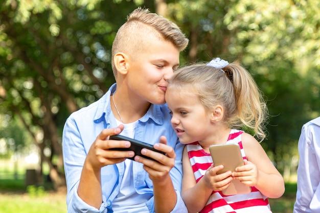 Милый ребенок с телефонами сидит на улице и использует гаджет - брат целует свою сестру в щеку