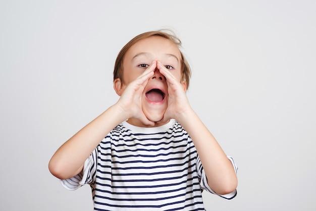 白い背景の上で叫んでかわいい子供。口を大きく開けて頬に手をつないでいる少年。子供の叫び。感情と表現に直面します。