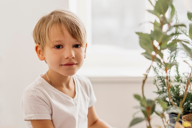 Cute child sitting next to plant at home