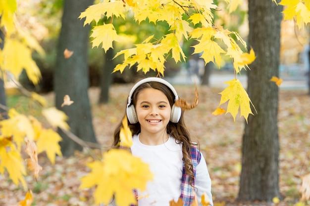 Милая улыбка ребенка со стереонаушниками. мелодия осени. школьница, слушая современные наушники. технология наушников. падающие листья. счастливый маленькая девочка носить наушники осень фон природа.
