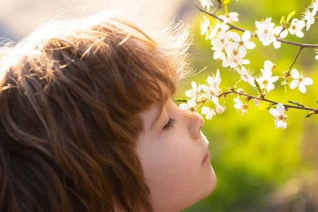 Cute child sniffs blooming tree summer kid in blossom garden