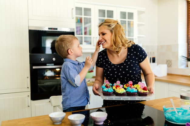 Cute child thankful to mother while preparing cookies in kitchen