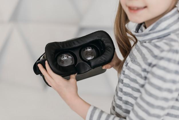 Милый ребенок, использующий гарнитуру виртуальной реальности высокий вид