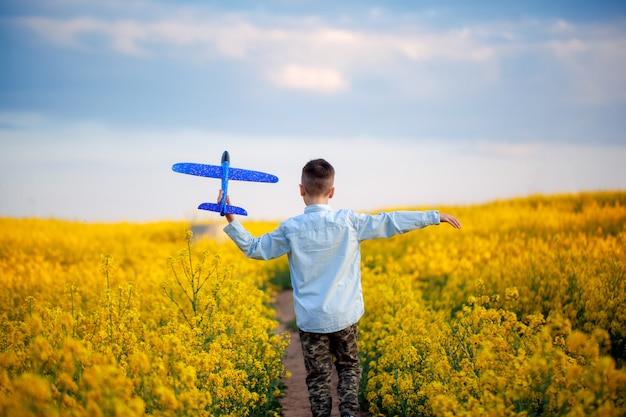 Милый ребенок гуляя в желтое поле на солнечный летний день. мальчик начинает бумажный самолетик. вид сзади