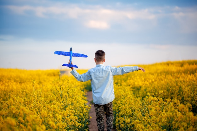 Cute child walking in the yellow field on a sunny summer day. boy starts paper plane. back view