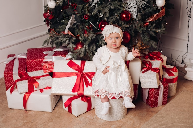 Cute child in white dress posing under christmas tree.