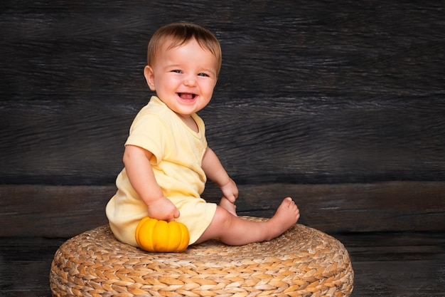 Cute child with the baby pumpkin smiling on the straw table on the wooden background