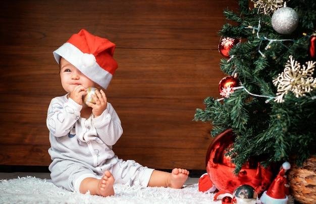 クリスマスツリーとかわいい子。モミの木の近くに座って、クリスマスの飾りを持ってそれをかじる幸せな赤ちゃん