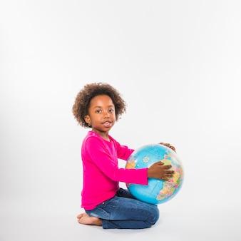 スタジオで地球儀を持つかわいい子供
