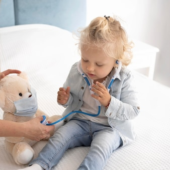 Cute child with toy and stethoscope at home during quarantine